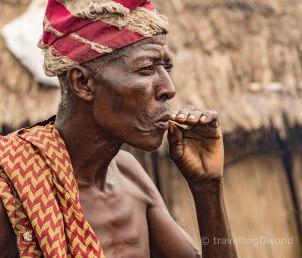 Hombre Holi con tatuajes faciales fumando un pitillo, Benin